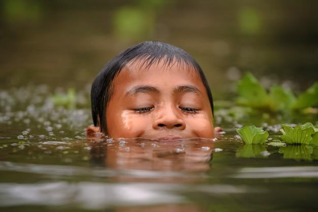 ダムヌンサドゥアック水上マーケットの近くのカナルで泳いでいる少年