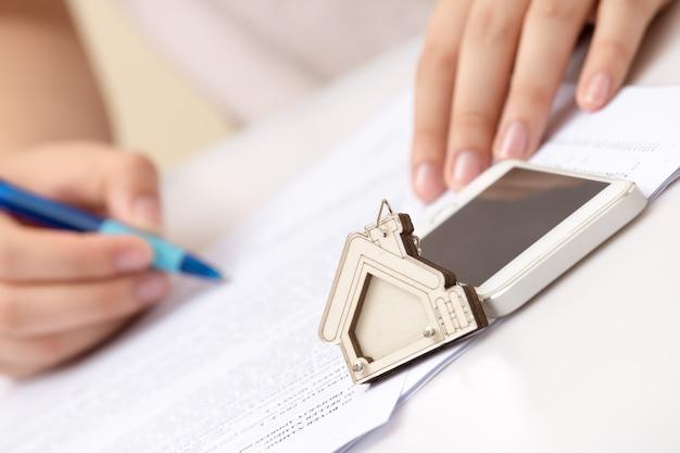 Рука женщины и домашний ключ. подписан договор и ключи от имущества с документами. концепция бизнеса в сфере недвижимости.