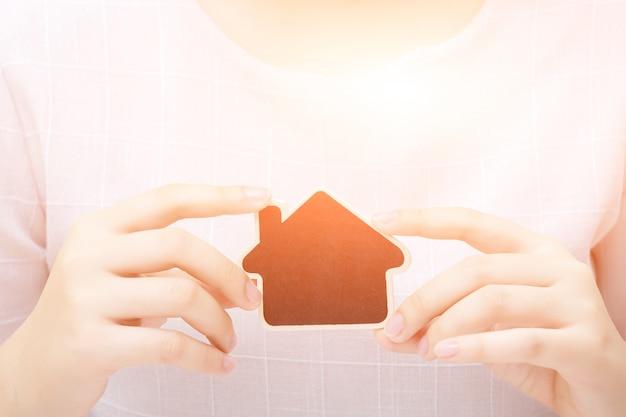 小さな家を持つ女性。不動産事業のコンセプトです。