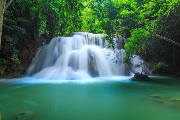 Водопад хуай мэй камин в национальном парке хуян сринагариндра. красивый и знаменитый водопад в глубоком лесу, провинция канчанабури, таиланд