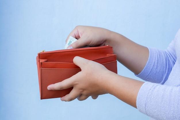 女性の手は財布から紙幣を引っ張る