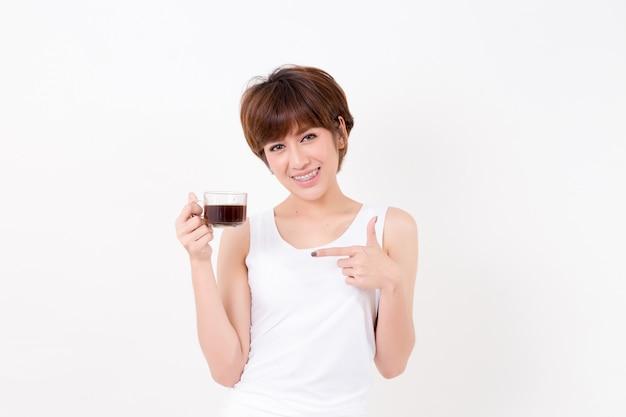 ホットコーヒーのカップを持つ美しい若いアジア女性。健康のための概念。