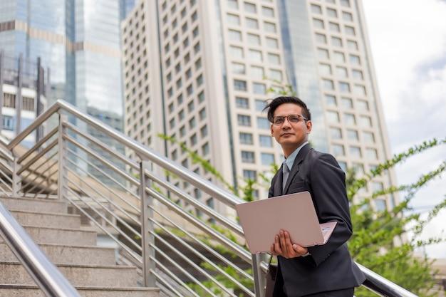 仕事にラッシュアワーに階段を上る彼のラップトップを持つビジネスマン。急いでください。