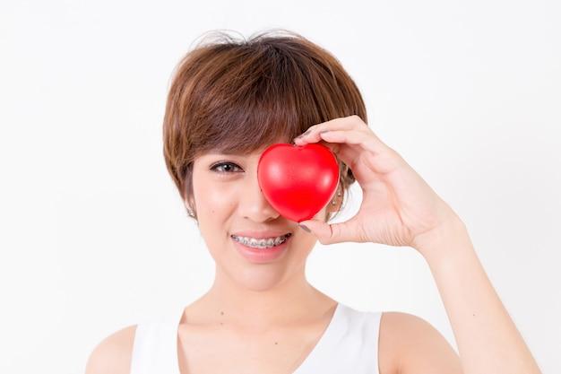 Красивая молодая женщина азии с красным сердцем. концепция для здорового.