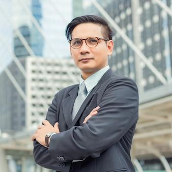 Азия молодой деловой человек перед современным зданием в центре города. концепция молодых деловых людей