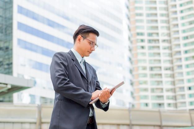 屋外の彼のラップトップコンピューターとの訴訟で若いアジア系のビジネスマン