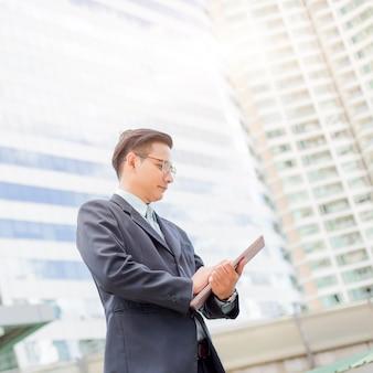 Молодой бизнесмен азии в костюме с его портативным компьютером на открытом воздухе