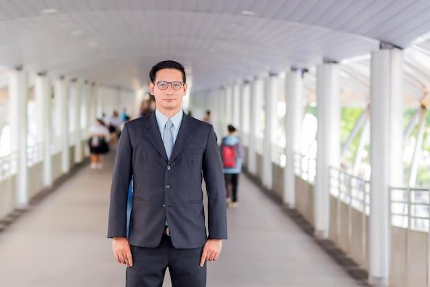 Бизнесмен молодой азии красивый с его стеклами стоя на дорожке современного города.