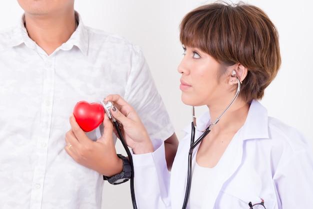 医者は心電図ラインと聴診器で赤いハートをチェックします。健康のためのコンセプト