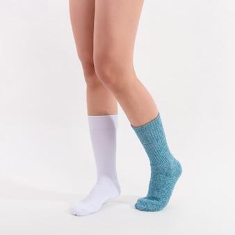 美しい女性の足に白と青の綿の靴下。白い背景に分離されました。スタジオの照明