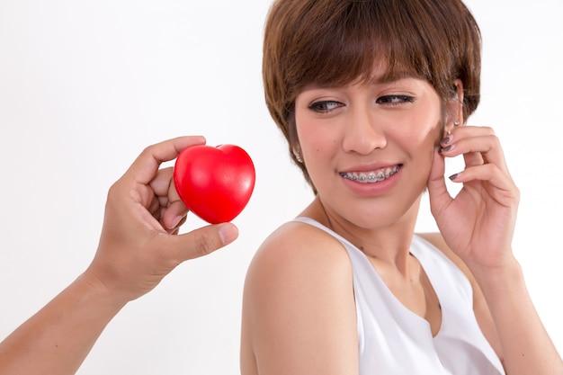 Красивая молодая женщина азии с красным сердцем. изолированные на белом фоне