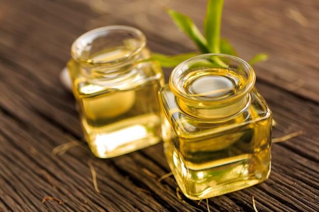 アロマエッセンシャルオイルまたはスパのボトルと天然の緑の木のテーブル