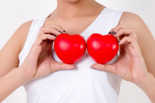 Красивая молодая женщина азии с красными сердцами. изолированные на белом фоне