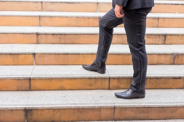 仕事にラッシュアワーに階段を上るビジネスマン