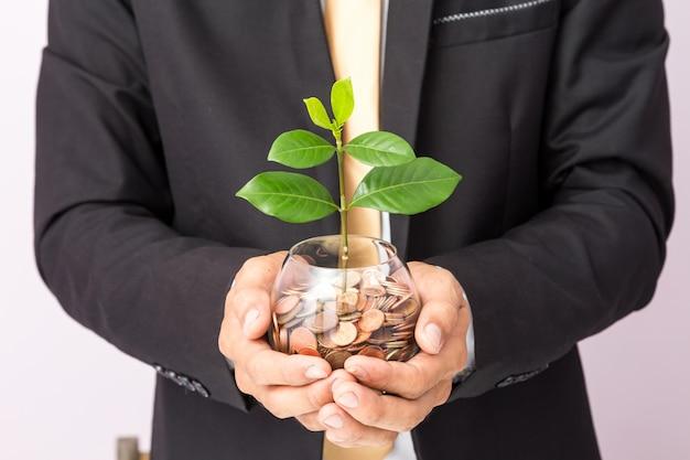 ガラスの上のコインと植物を置くビジネスマン手