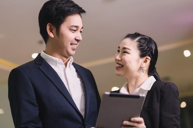 Счастливая пара бизнес с планшета
