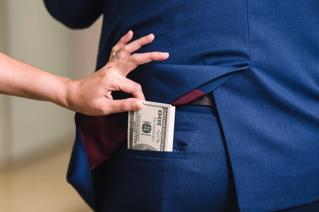 女性はビジネスマンからお金を盗んでいます