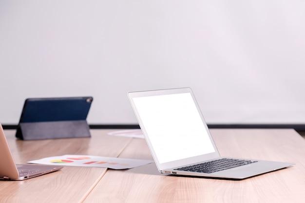 Планшет и ноутбук на столе в конференц-зале