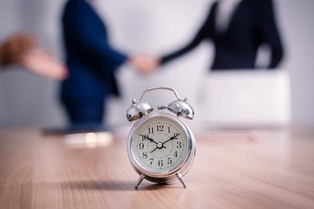 セミナー室のビジネス人々とテーブルの上の目覚まし時計。企業の成功ブレインストーミングチームワークを満たす
