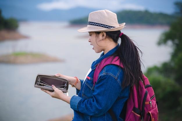 旅行人のコンセプトです。アジアの女の子の肖像画は空の財布を開く