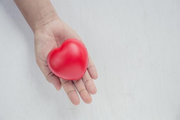 Красное сердце на руке у девушки