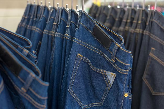 Многие джинсовые джинсы висят на стойке
