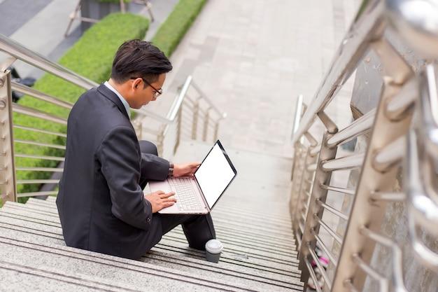ビジネスの男性は現代都市の屋外彼のラップトップで働いています。