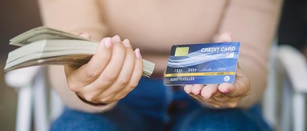 アジアの若い女性は、クレジットカードで支払うか、コーヒーショップで現金を支払うかを決定します。