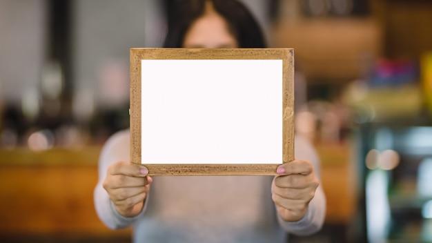 コーヒーショップで空白の木製フレームを保持している女性