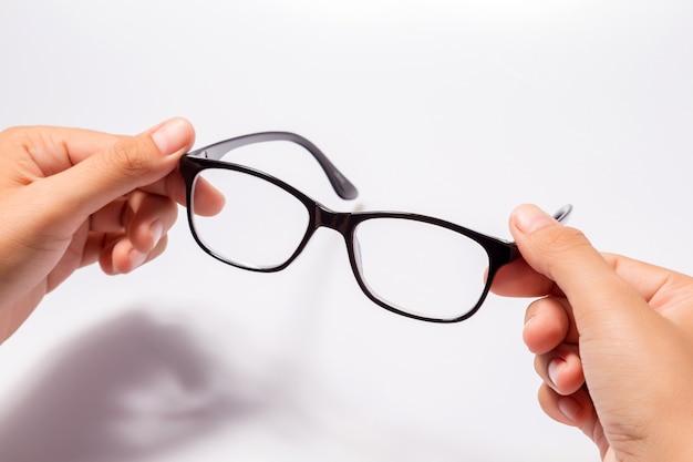 Женщина, держащая черные очки в очках с блестящей черной рамкой, изолированная на белом