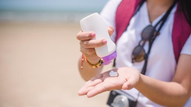 Женские руки с солнцезащитным кремом на пляже.