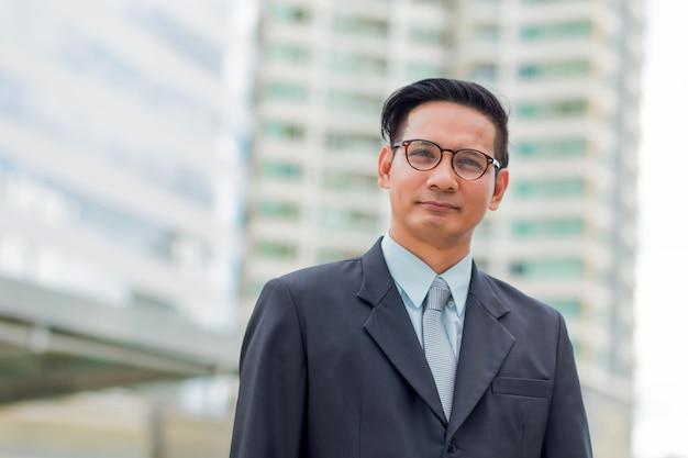 ダウンタウンのモダンな建物の前にアジアの若いビジネスマン若いビジネスマンの概念