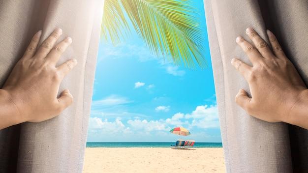 人と希望のコンセプト。窓のカーテンを開き、青い空の下でビーチを見ている男