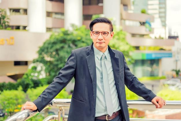 ダウンタウンのモダンな建物の前にアジアの若手実業家