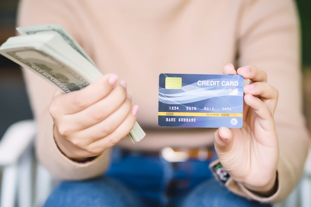 アジアの若い女性は、コーヒーショップでのクレジットカードまたは現金による支払いを決定しています