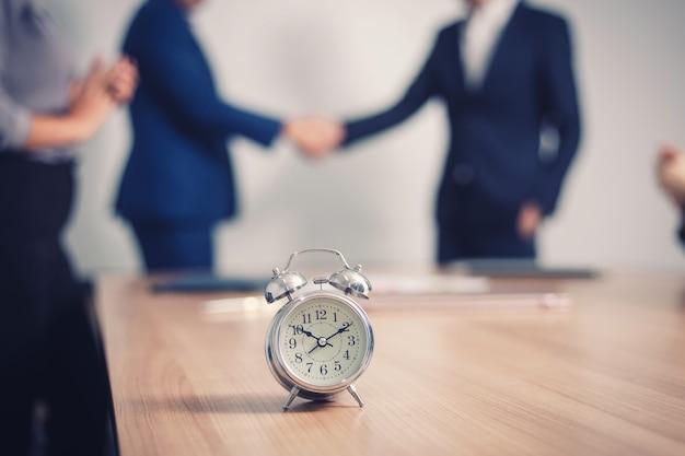 セミナー室のビジネス人々とテーブルの上の目覚まし時計。