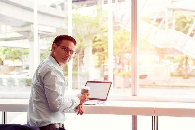 Бизнесмен азии держа горячую кофейную чашку и работая с компьтер-книжкой пока сидящ кафе