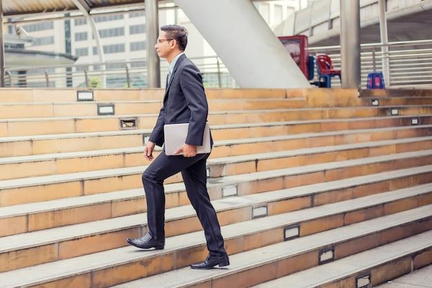 仕事にラッシュアワーに階段を上る彼のラップトップを持つビジネス男