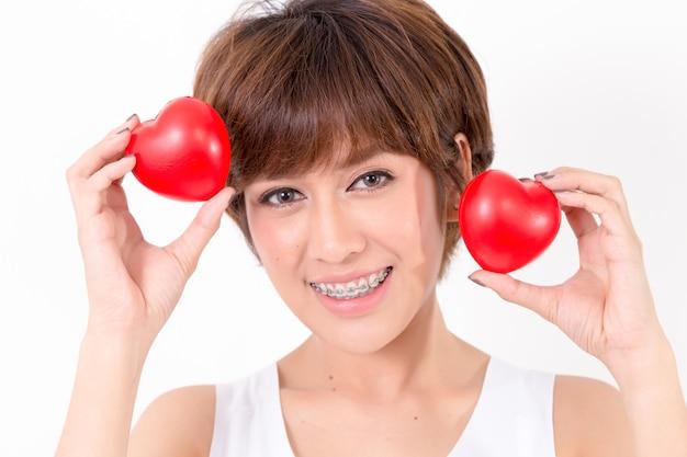 赤いハートを持つ美しい若いアジア女性。