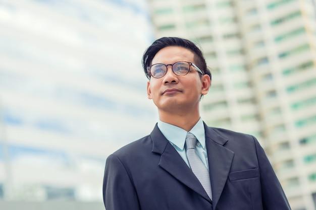 Азия молодой деловой человек перед современным зданием в центре города