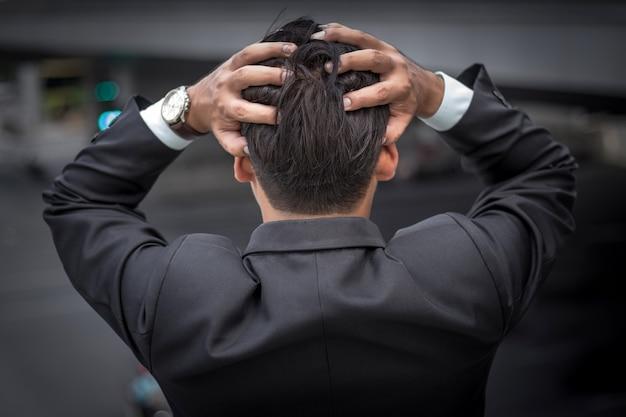 ビジネスの男性は彼の仕事の後に疲れているか強調しました。
