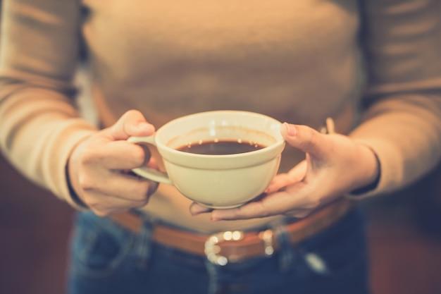 Молодая женщина держит чашку горячего кофе в природе