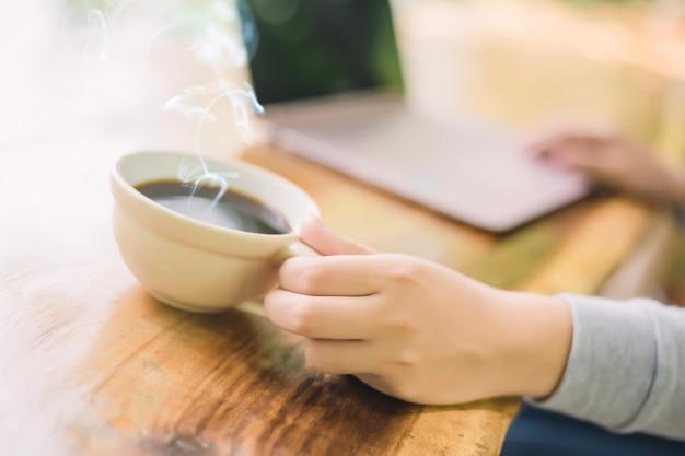 木製のテーブルでコーヒーショップに座って、コーヒーを飲みながら、ラップトップを使用しての若い女性。