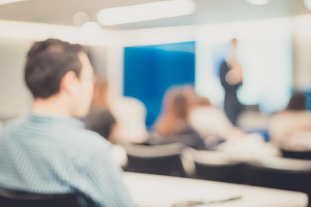 企業のビジネス会議で講演をしているスピーカーの焦点が外れます。