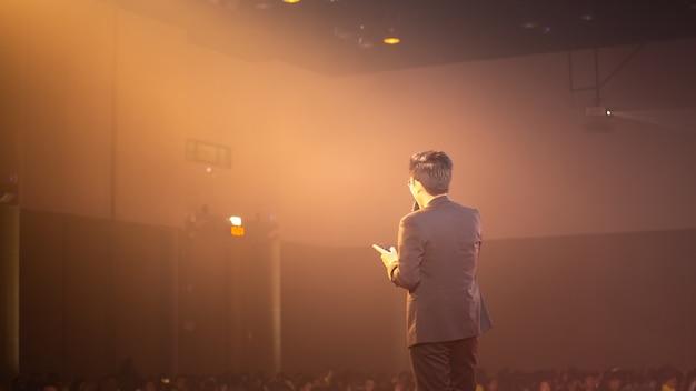 ステージ上のスピーカーとセミナー室でのビジネスについて話す