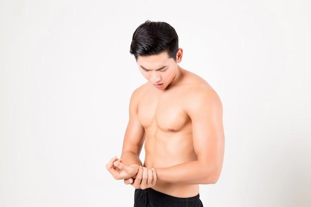 痛みを感じる腕を持つ男。白で撮影スタジオ。フィットネスと健康の概念