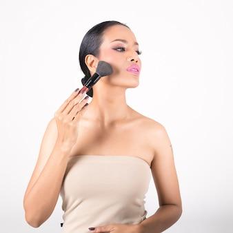 化粧。メイクアップクローズアップを適用します。メイクアップ用化粧品パウダーブラシ。