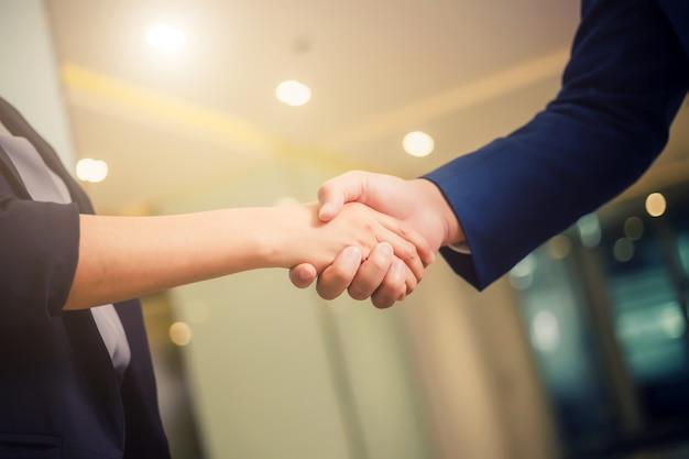 セミナールームでの会議の間、握手ビジネス人々