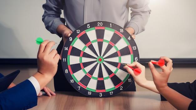 Бизнес-команда, указывая на дартс, направленных на целевой центр бизнеса, нацеливание бизнес-концепции