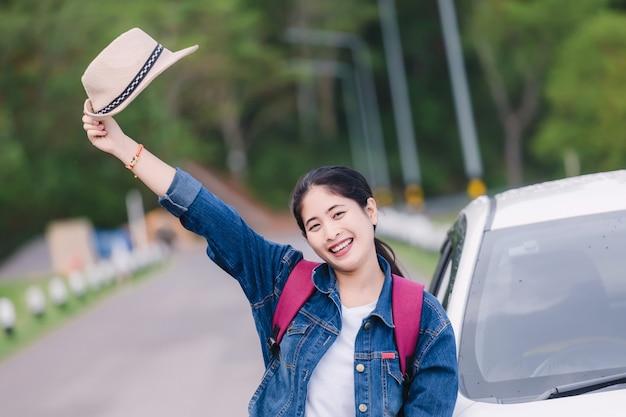 車の窓の外の自然の景色を見て夏のロードトリップ旅行休暇にリラックスした幸せな女